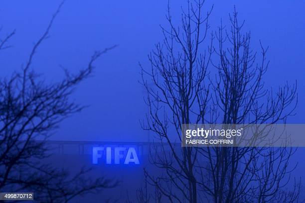 A sign of FIFA is seen on the top of its headquarters engulfed by fog on December 3 2015 in Zurich The multimillion dollar corruption scandal...