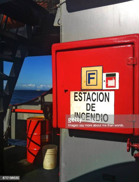 Sign of fire extinguisher inside the ferry-boat to Chiloé. A ship appears at the horizon.