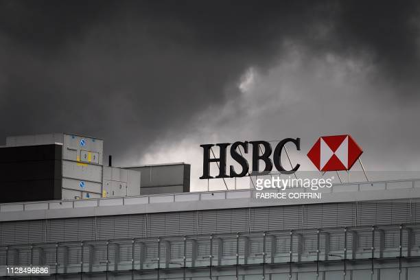 A sign of international banking and financial services holding company HSBC is seen under black clounds on the top of a building on March 1 2019 in...