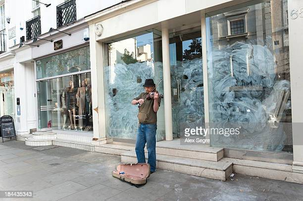 Sign of recession - a busker playing violin outside whitewashed window of a closed down shop in King's Road, Chelsea, London