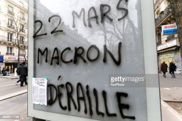 A sign on a billboard reading « March 22 Macron has veered off track » is seen during a demonstration in front of the Gare de lEst railway station in...