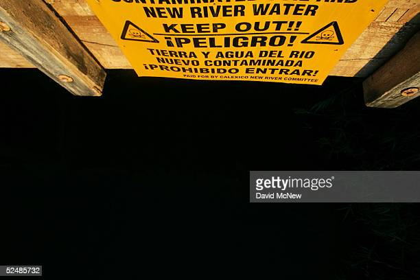 A sign on a bridge warns of the danger of entering the New River reportedly the most polluted river in the US and down which illegal immigrants float...