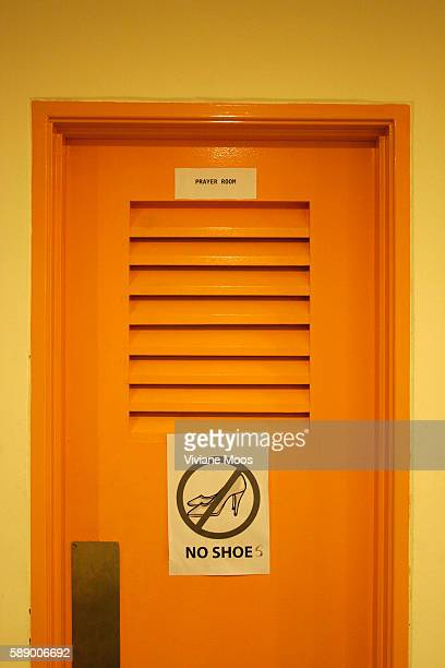 Sign on a door of the women's prayer room in the Kuala Lumpur Performing Arts Centre showing that shoes are not allowed