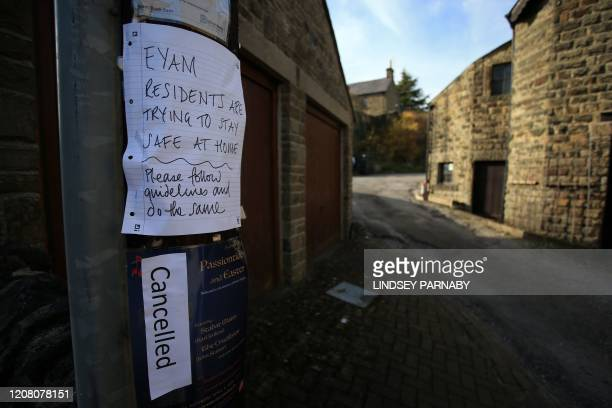 A sign on a lamp post asking people to stay at home and observe the guidelines on social distancing is seen in the village of Eyam in Derbyshire...