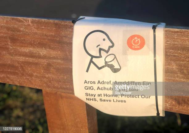 A sign on a park bench written in both the Welsh and English language urges people to stay at home to protect the NHS on the Cardiff Bay barrage on...