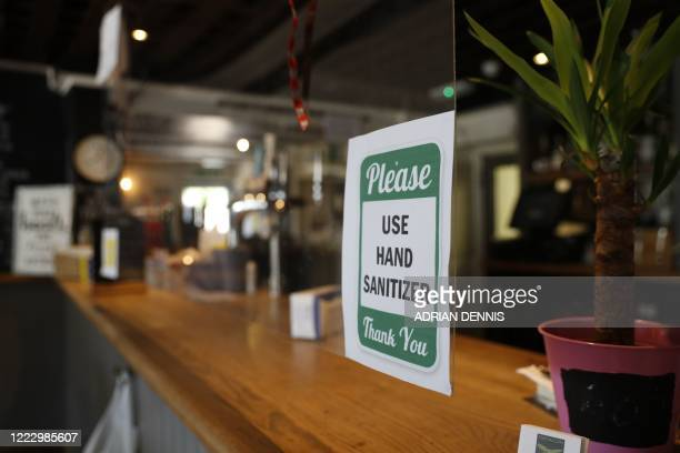 Sign on a plastic 'sneeze screen' at the bar asks customers to use hand sanitizer as a precaution against spreading the novel coronavirus inside The...