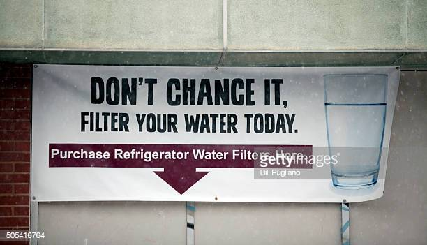 A sign on a the front of a building warns residents to filter their water January 17 2016 in Flint Michigan US President Barack Obama declared a...