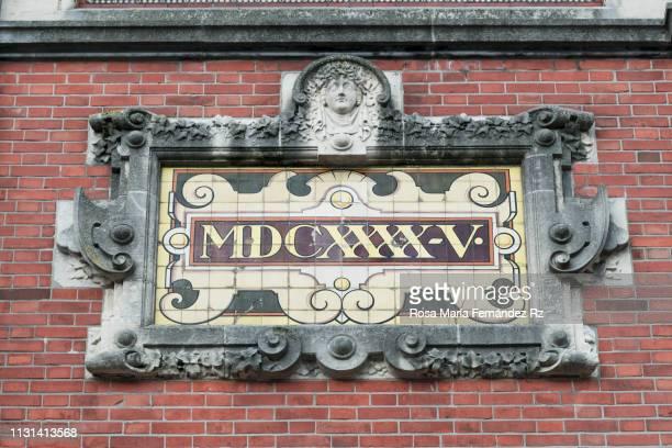 """sign on brick wall reads """"1645"""" written in roman numeral. - algarismo romano imagens e fotografias de stock"""