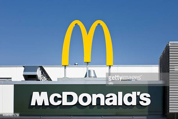 sign on mcdonalds store against blue sky - mcdonald's stock pictures, royalty-free photos & images