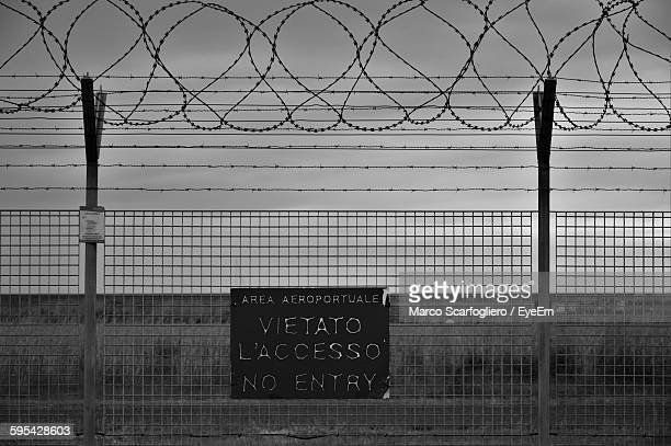 Sign On Metallic Fence Against Sky