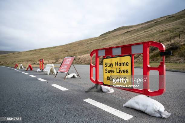 Sign on the A470 near Pen y Fan warns motorists to stay at home to save lives on March 28 in Brecon, Wales. Last weekend the area was busy with...