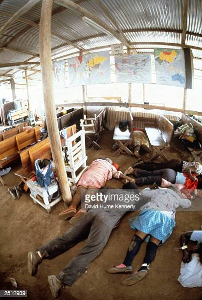 A sign on the back wall reading 'love one another' hangs over the bodies of Reverend Jim Jones' followers on the floor of the People's Temple Cult...