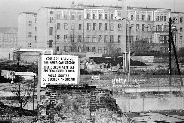 A sign on the Berlin Wall on Wilhelmstrasse Berlin in English Russian French and German 1961 It warns 'You are leaving the American Sector'