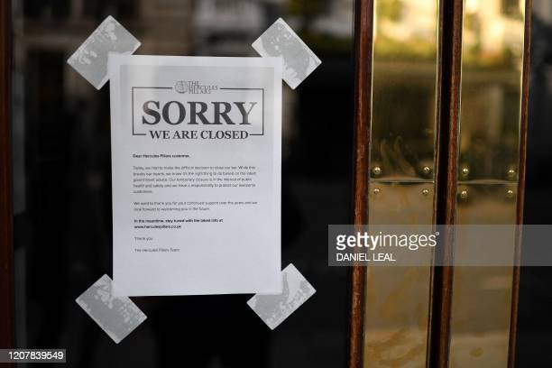 A sign on the door of a pub notifies customers that it will be temporarily closing the bar in London on March 20 during the ongoing coronavirus...
