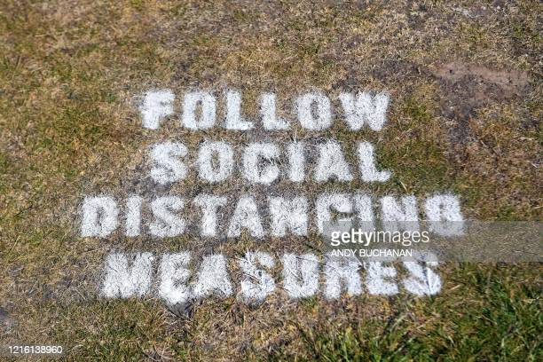 A sign on the grass reminds golfers to respect social distancing measures at The Old Course in St Andrews Scotland on May 29 as the Scottish...