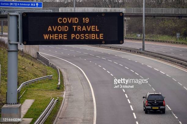 Sign on the M8 motorway advises motorists to avoid travel where possible on March 24, 2020 in Glasgow, Scotland. First Minister of Scotland Nicola...