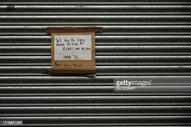 """Sign on the shutters of of shop, closed dowm due to COVID-19, reads """"We Will Be Open Again As Soon As Boris Says We Can"""", at Kirkgate market in..."""