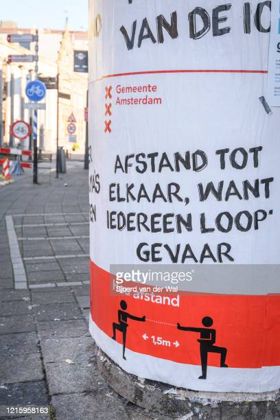Sign on the street in Amsterdam advicing to keep your distance because we are in danger following the advice of the Dutch government to stay at home...