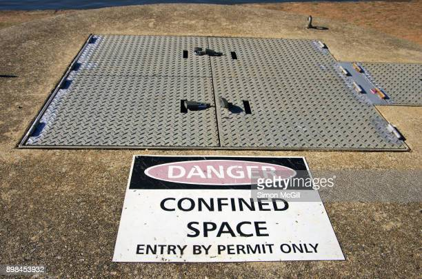 danger: confined space. entry by permit only sign on the water pumping station at gallipoli reach, canberra, australian capital territory, australia - confined space stock pictures, royalty-free photos & images