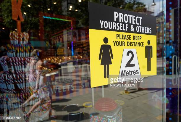 Sign outside a shop asks customers to social distance on Oxford Street in central London on June 7, 2021. - The Delta variant of the coronavirus,...