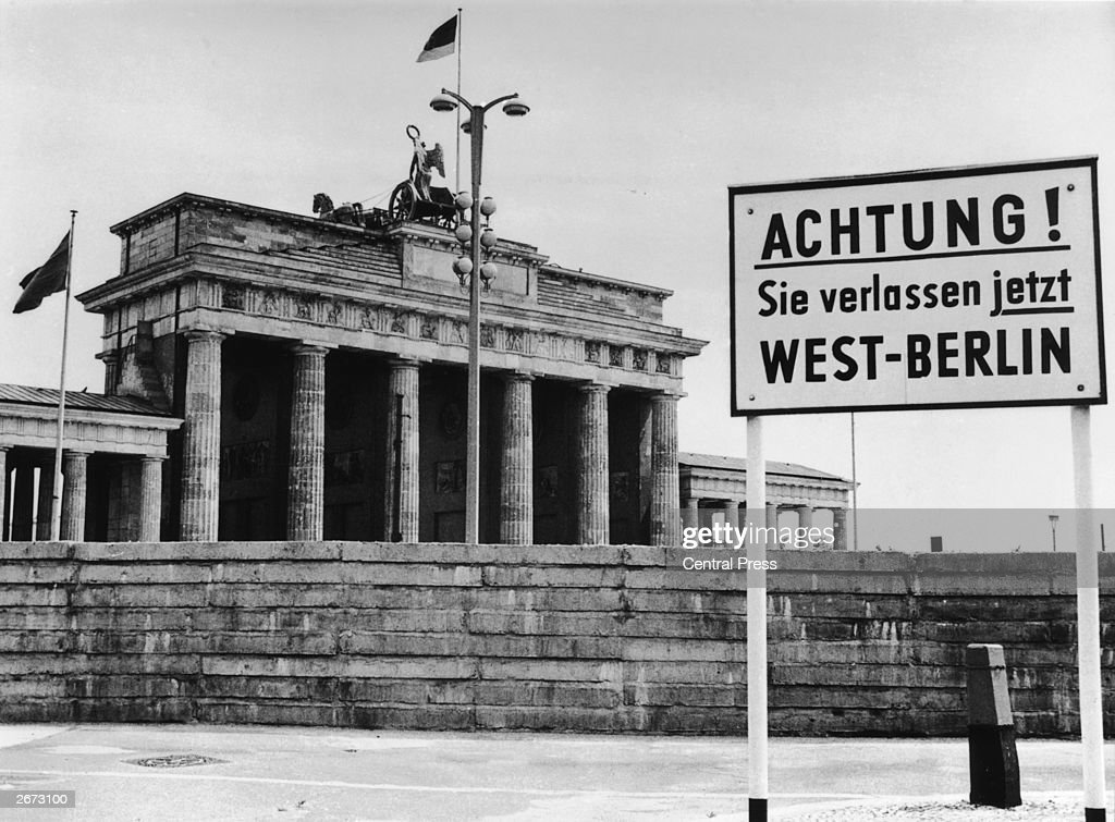 A sign outside the Brandenburg Gate and the Berlin Wall reading 'Attention! You are now leaving West Berlin'.