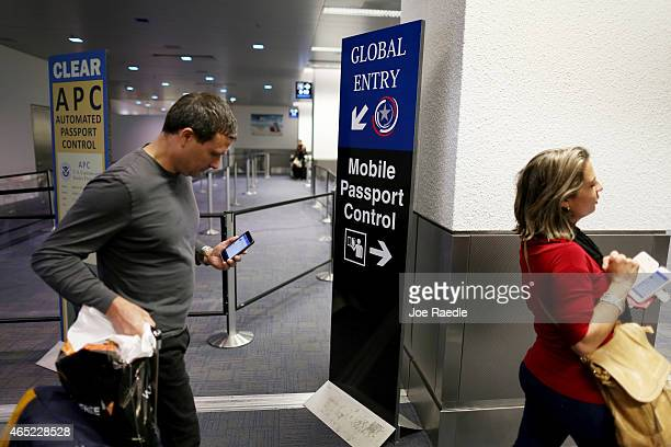 A sign points passengers to the mobile passport control window set up for international travelers arriving at Miami International Airport on March 4...