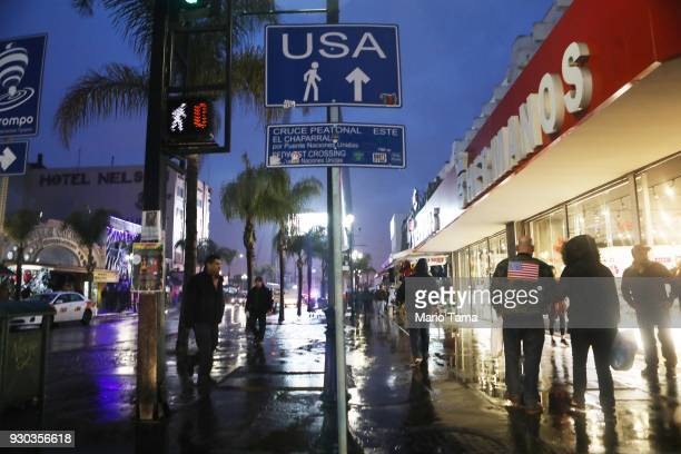A sign points to the pedestrian crossing to the US as man walks past wearing an American flag on his jacket near the US/Mexico border on March 10...