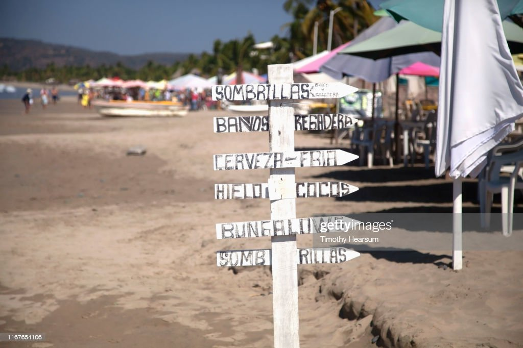 Sign post in Spanish with a sea of umbrellas beyond on a beach on Tenacatita Bay, Costalegre, Jalisco, Mexico : Stock Photo