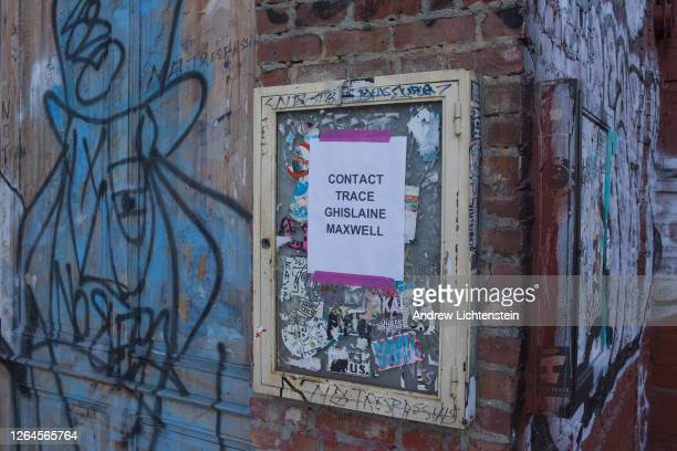 A sign posted on a graffiti covered wall calls for the contract tracing go Ghisliane Maxwell child molester Jeffrey Epstein's fixer on May 31 2020 in...