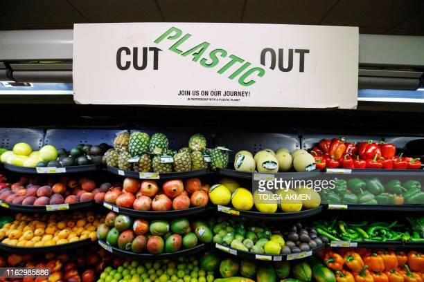 A sign promoting plastic free packaging is seen above a display of loose fresh fruit at Budgens supermarket in Belsize Park north London on July 2...