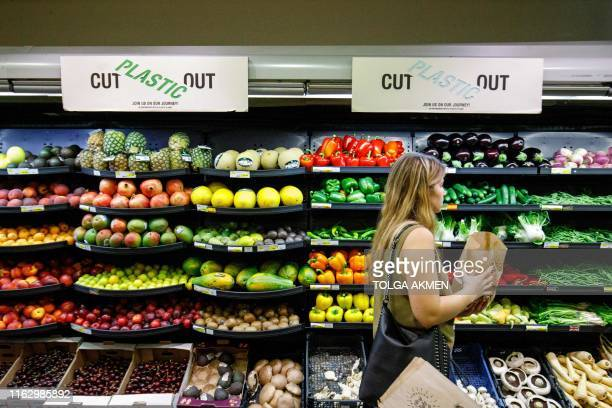 Sign promoting plastic free packaging is seen above a display of loose fresh fruit as a shopper browses at Budgens supermarket in Belsize Park, north...