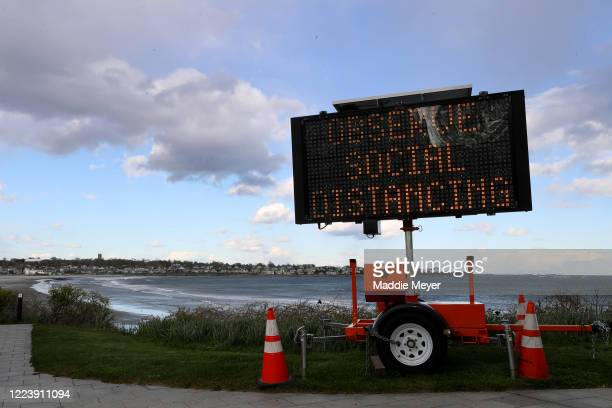 Sign promoting social distancing at the entrance to the Cliff Walk on May 09, 2020 in Newport, Rhode Island. Non-critical retail establishments began...