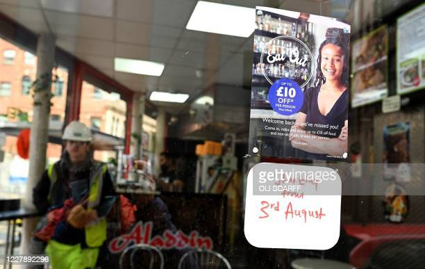 """Sign promoting the British Government's """"Eat out to Help out"""" COVID-19 scheme to get consumers spending again, is pictured outside a restaurant in..."""