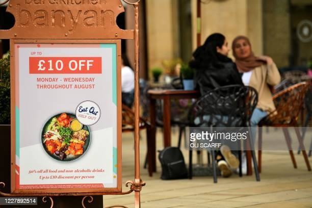"Sign promoting the British Government's ""Eat out to Help out"" COVID-19 scheme to get consumers spending again, is pictured outside a restaurant in..."