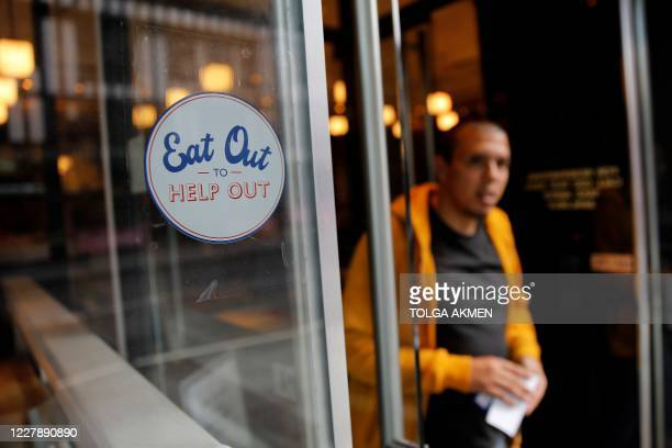 "Sign promoting the British Government's ""Eat out to Help out"" coronavirus scheme to get consumers spending again, is pictured in the window of a..."