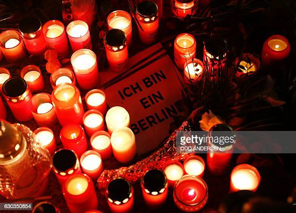 TOPSHOT A sign quoting John F Kennedy's sentence 'I am a Berliner' lies inmid candles at a makeshift memorial in front of the...