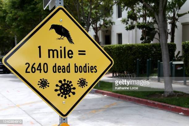 A sign reading 1 mile = 2640 dead bodies with renderings of the coronavirus molecule is left posted at an intersection on June 01 2020 in Westwood...