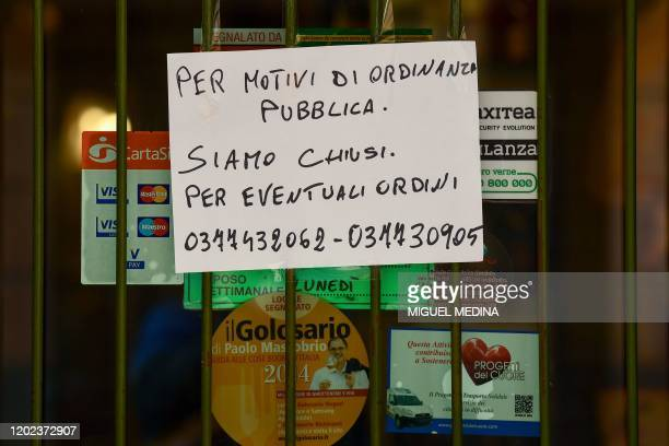 A sign reading Closed by Municipal Decree for any orders call the following numbers is put up on a shop's window in Codogno southeast of Milan on...