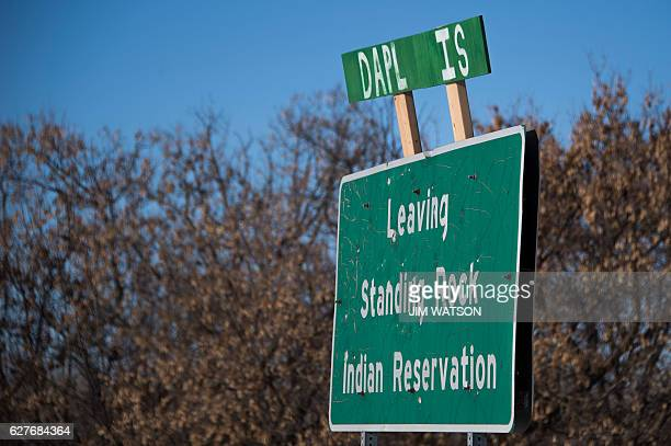 A sign reading DAPL IS is added to a road sign reading Leaving Standing Rock Indian Reservation next to the Oceti Sakowin Camp on the edge of the...