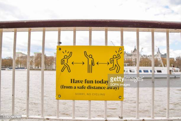 Sign reading 'Have Fun Today From A Safe Distance Away' seen on the Queen's Walk promenade in London. New social distancing signs have been added...