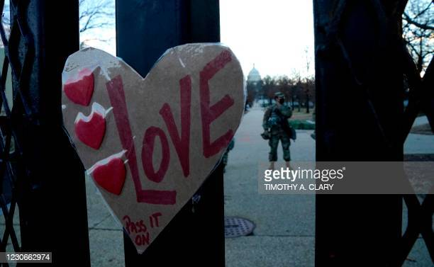 "Sign reading ""Love"" is placed on a barrier outside the US Capitol as National Guard troops stand guard ahead of the inauguration ceremonies for..."