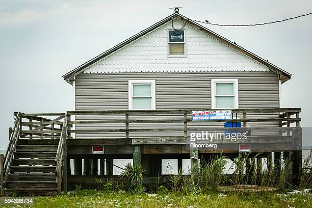 A sign reading No Retreat Save the Bayshore Communities hangs on the porch of a home in Delaware Bay New Jersey on Tuesday June 28 2016 Through the...