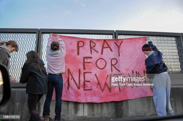 Sign reading 'Pray for Newtown' is hung above interstate following shooting at Sandy Hook Elementary school where Adam Lanza opened fire inside...