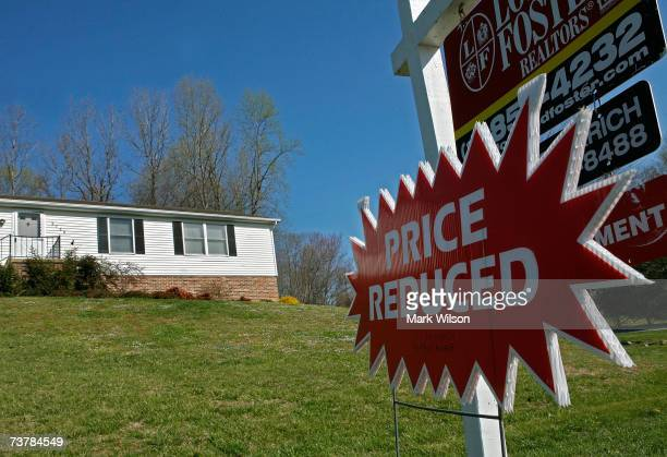A sign reading 'Price Reduced' hangs below a for sale sign in front of a house April 3 2007 in Chesapeake Beach Maryland Although the US stock market...