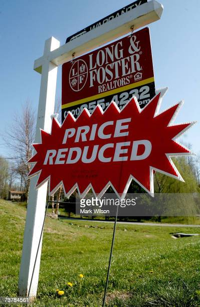 A sign reading Price Reduced hangs below a for sale sign in front of a house April 3 2007 in Chesapeake Beach Maryland Although the US stock market...