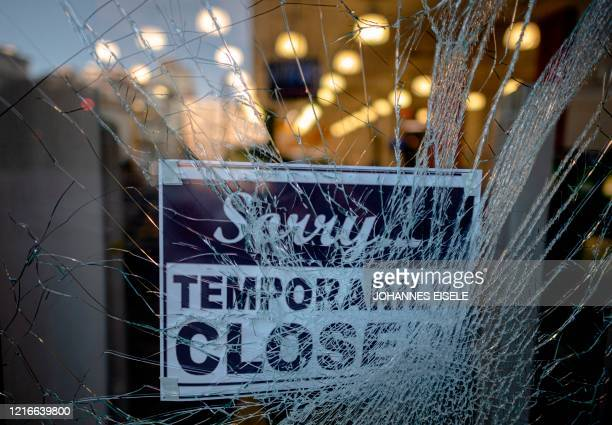 A sign reading sorry temporarily closed is seen behind a shattered glass of a storefront after a night of protest over the death of AfricanAmerican...