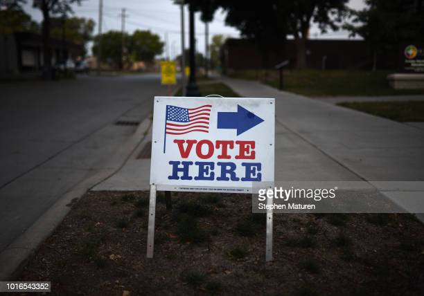 "Sign reading ""Vote Here"" points toward a polling place for the 2018 Minnesota primary election at Holy Trinity Lutheran Church on August 14, 2018 in..."