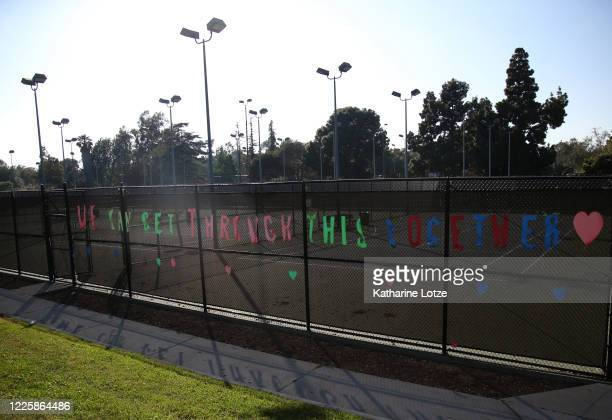 A sign reading We can get through this together hangs on the side of the tennis courts at the Cheviot Hills Tennis Center on May 11 2020 in Los...
