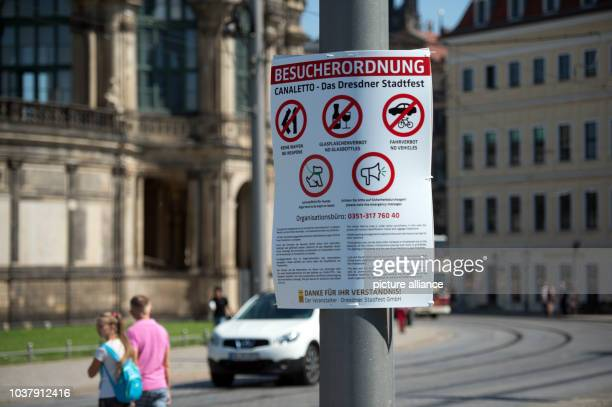A sign reads Besucherordnung Canaletto Das Dresdner Stadtfest featuring various prohibition symbols on a lamppost in the old town in Dresden Germany...