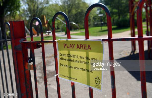 A sign reads Due to COVID19 this play area will be closed until further notice on the gates of a childrens' play area in Abbey Park in Leicester...